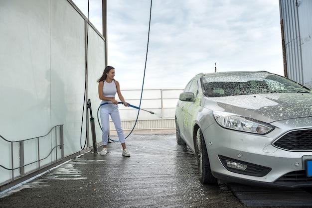 スプレーフォーム付きのホースを使用して車を汚れからきれいにする性的な若いスリムな女性。クリーニングコンセプト