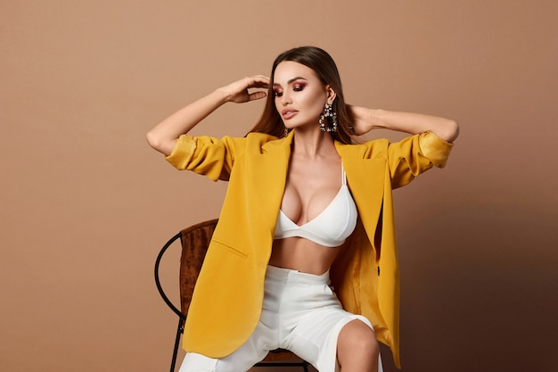 Sexy adult woman in the stylish yellow blazer posing