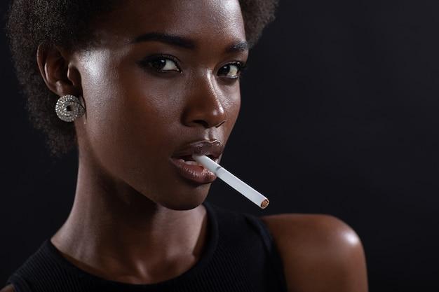 Сексуальная афро-американская женщина курит сигарету на черном фоне