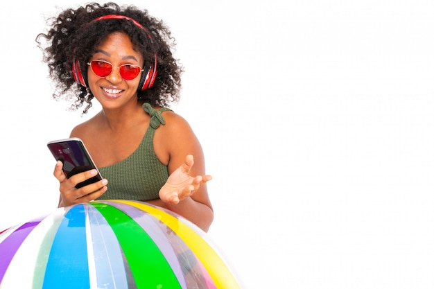 Sexy african woman in sunglasses and a swimsuit holds the phone in her hands and listens to music