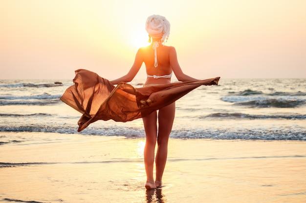 豪華なショールパレオシフォンドレスを着たターバンと水着のセクシーで美しい若い女性が風に乗って成長します。ビーチのそばの海の自由に沈む夕日。