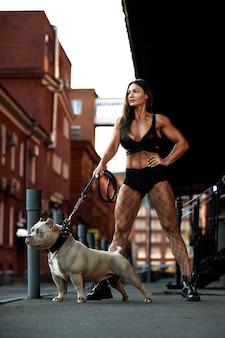カメラを見て、街の通りでいじめっ子犬とポーズをとるセクシーで間違ったブルネットの女性。