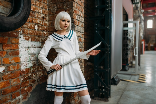 Sexy anime style blonde lady with sword. cosplay fashion, asian culture, doll with blade, cute woman with makeup in the factory shop