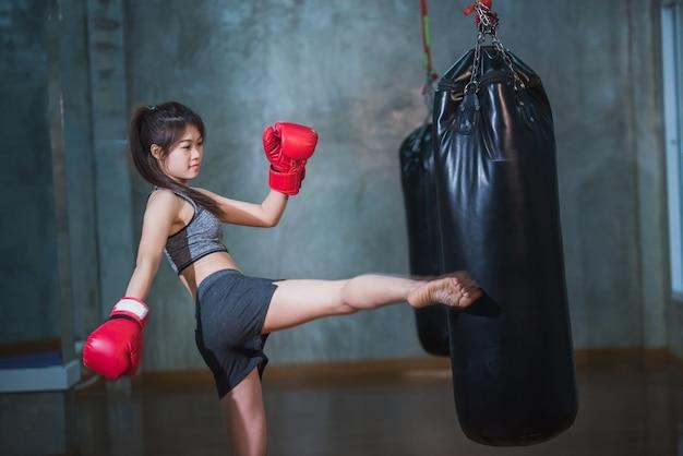 Sexy asia girl punching boxing bag