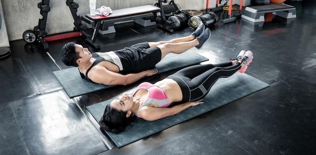 Сексуальная азиатская женщина и красивый мужчина упражнения на коврики для йоги в тренажерном зале.