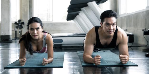 セクシーなアジアの女性とハンサムな男性がジムでヨガマットで運動しています。