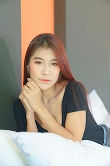 Сексуальная азиатская женщина в черном бикини, лежа на кровати