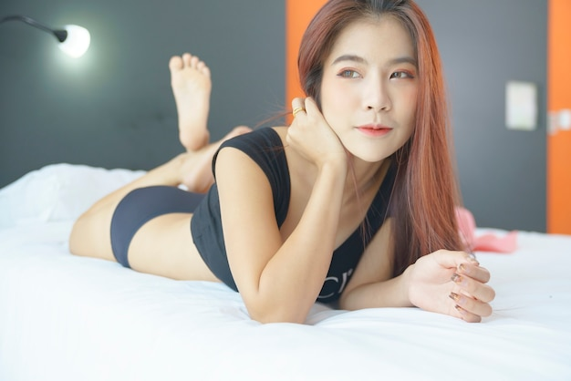 ベッドに横たわっているビキニ黒のセクシーなアジアの女性