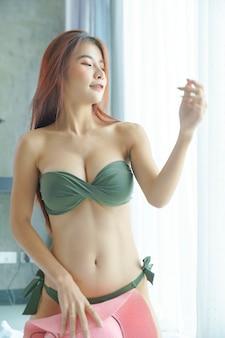 Сексуальная азиатская женщина в зеленом бикини, держащая розовую шляпу в спальне