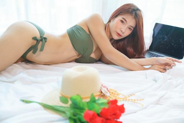 Сексуальная азиатская женщина в зеленом бикини, лежа на кровати