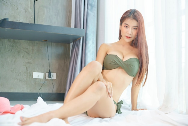 Сексуальная азиатская женщина в зеленом бикини на спальне в праздник
