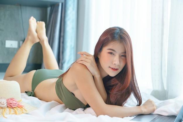 Сексуальная азиатская женщина в зеленом бикини работает на ноутбуке на кровати