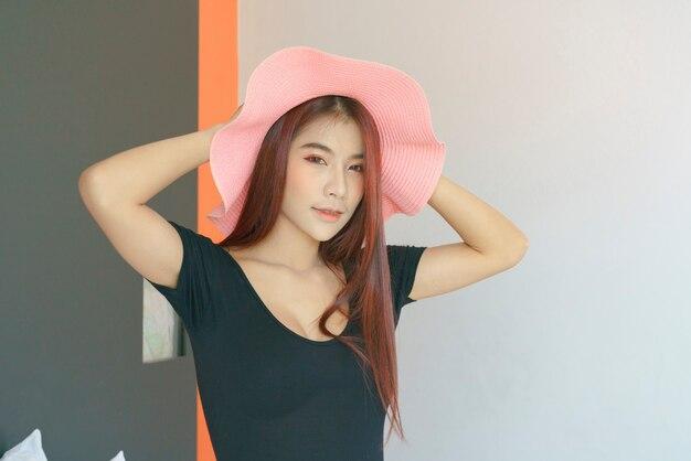 Сексуальная азиатская женщина в черной рубашке лежа и носить розовую шляпу