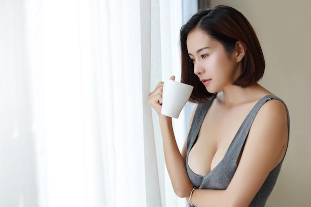 窓際に立ってコーヒーを飲むセクシーなアジアの女性