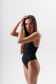 제기 무기와 흰색 스튜디오 배경에 검은 란제리에 포즈를 취하 긴 머리를 가진 섹시 아시아 여자. 매력적인 여성 서. bodysuit에서 마른 여자의 모델 테스트