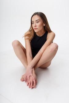 맨발로 흰색 스튜디오 배경에 검은 란제리 포즈 긴 머리를 가진 섹시 아시아 여자. 그녀의 무릎이 구부러진 바닥에 앉아 매력적인 여성. bodysuit에서 마른 여자의 모델 테스트