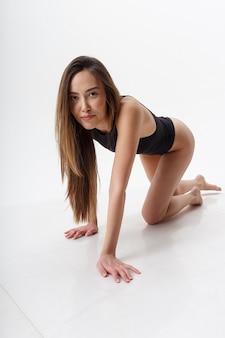 素足で白い壁に黒いランジェリーでポーズをとる長い髪のセクシーなアジアの女性。彼女の膝の上に床に立っている魅力的な女性。ボディスーツのスキニー女性のモデルテスト
