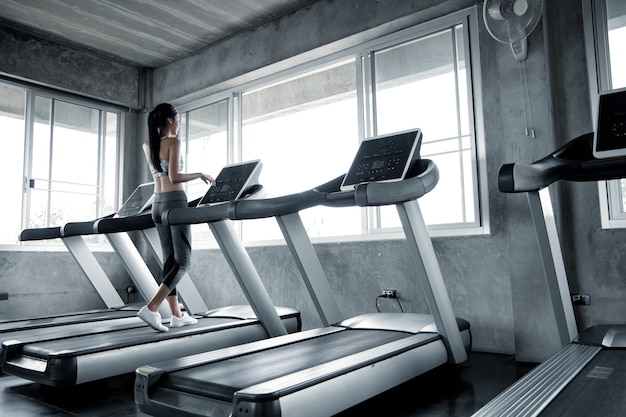 Sexy asian women exercising on the running machine in the gym. woman workout in gym healthy. concept of health care with exercise in gym. beautiful girl playing fitness in the gym.