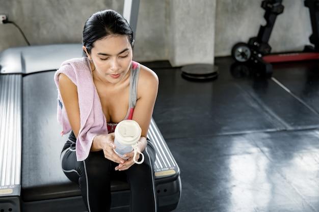 Сексуальные азиатские женщины держат фляжку, сидят и отдыхают уставшие на беговой дорожке после тренировки. фитнес в тренажерном зале. позаботьтесь о своем здоровье с помощью упражнений. здоровый уход с концепцией тренировки.