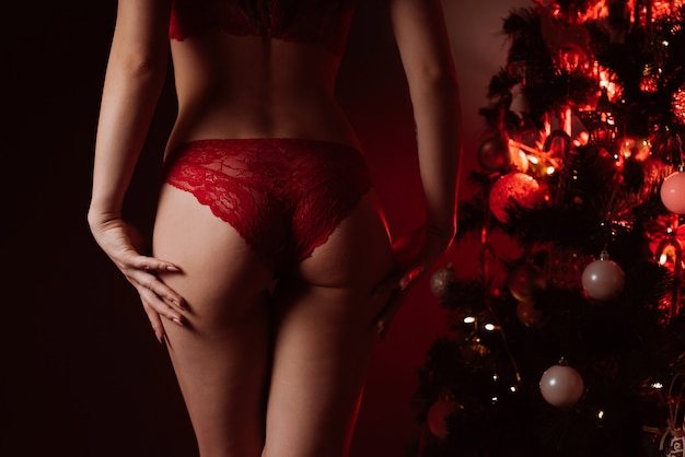 Sexy ass of a girl in red panties next to the christmas tree at the new year celebration