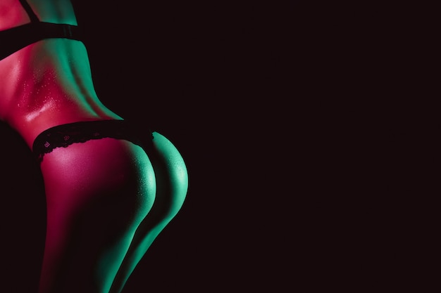 Sexy ass of woman in panties with drops of water and sweat on her body. slim beautiful female body in underwear with neon light on black background with copy space