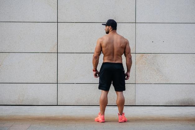 セクシーなアスリートが壁に背を向けて立っています。フィットネス。健康的な生活様式。