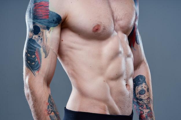 Сексуальная спортсменка с обнаженным торсом и накачанными мышцами татуировка на сером фоне модель