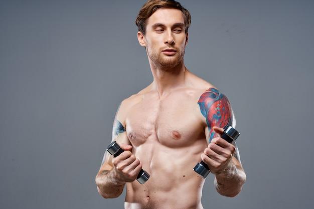 腕の筋肉と健康ビタミンダンベルモデルを強化したセクシーなアスリート