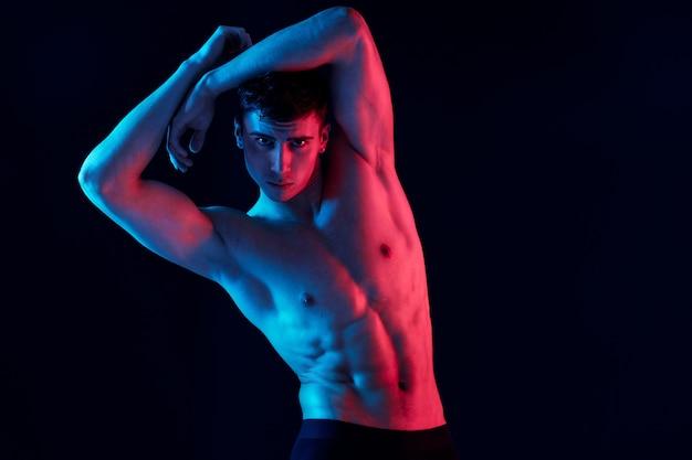 검은 배경에 머리 뒤에 손을 잡고 부풀린 몸통을 가진 섹시한 운동 선수