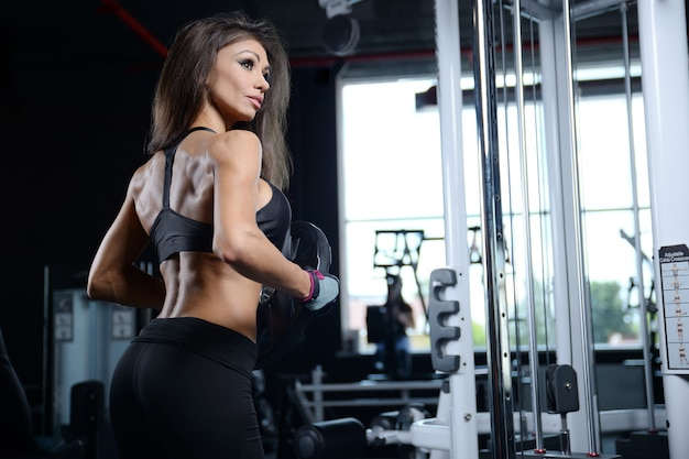 Sexy athletic young girl working out in gym
