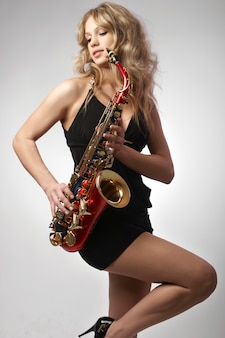 Sexy attractive blonde women with saxophone