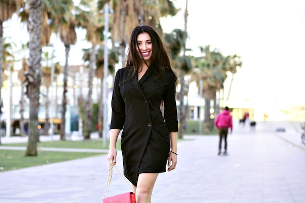 Сексуальная привлекательная уверенно женщина гуляет по улице с пальмами, минималистичный черный платье современной бизнес-леди, путешествуя по испании.