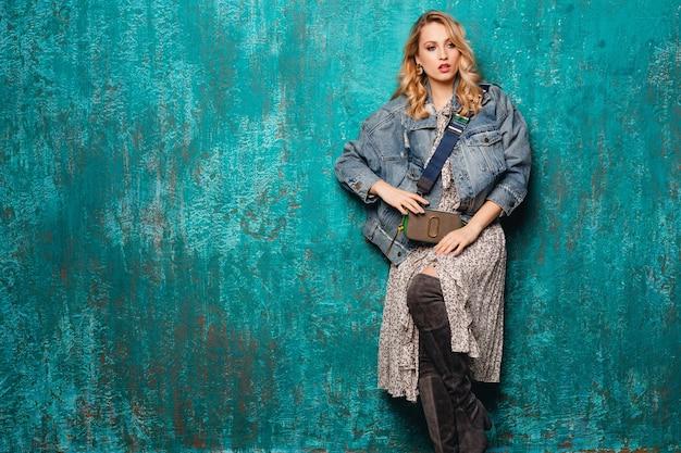 Сексуальная привлекательная стильная блондинка в джинсах и негабаритной куртке идет против старинной зеленой стены на улице