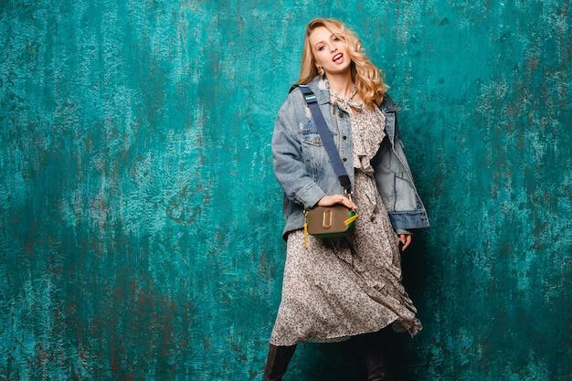 거리에서 빈티지 녹색 벽에 걸어 청바지와 특대 재킷에 섹시 매력적인 세련된 금발의 여자