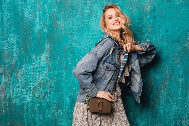 通りのヴィンテージの緑の壁に対して歩くジーンズと特大のジャケットのセクシーな魅力的なスタイリッシュなブロンドの女性