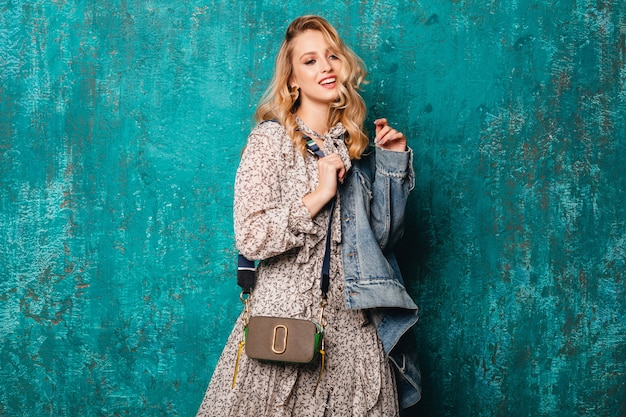 Sexy attractive stylish blonde woman in jeans and oversize jacket walking against vintage green wall in street