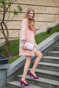 セクシーな魅力的なスタイリッシュな笑顔の女性がピンクのコート春のファッショントレンドの財布を持って街を歩く