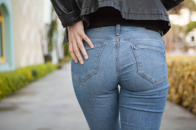 Sexy back or buttocks of a beautiful woman in jeans and leather jacket on blur background