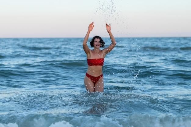 Сексуальная спина красивой женщины в красном бикини на фоне моря.
