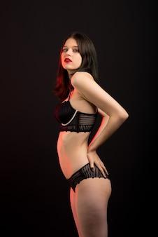 レースの下着を着たゴージャスなスリムボディのセクシーで美しく魅力的な女性が暗いスタジオでポーズを取っています。