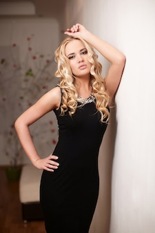 Sexy beautiful blond lady model in black dress standing near wall indoors