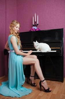 Сексуальная красивая белокурая девушка в платье играет на пианино с кошкой