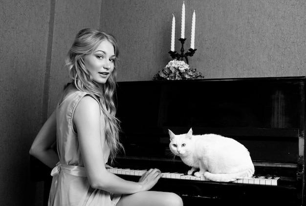 Сексуальная красивая блондинка в платье играет на пианино с кошкой