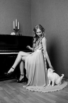 猫とピアノを弾くドレスのセクシーな美しいブロンドの女の子