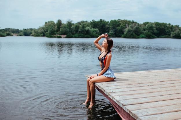 セクシーな美しいブルネットは、黒い水着で湖や川の近くの橋で日光浴をします。観光とレクリエーションの概念。