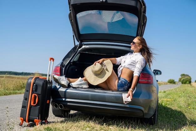 夏休みのセクシーな美しいヨーロッパのモデルと夏の風景の自然の中で豪華な自動車でポーズをとるサングラス。