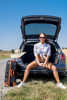 Sexy beautiful  european model in summer vacation and sunglasses posing in luxurious auto in nature in the summer landscape.