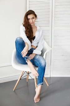 Sexy beautiful girl in jeans white shirt sitting