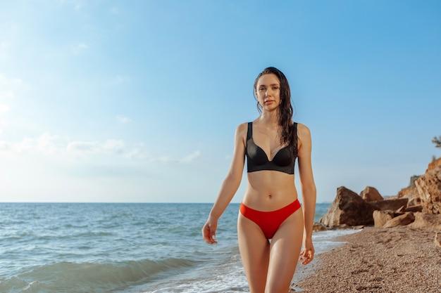 ビーチを歩いているセクシーな美しい少女。コピースペース
