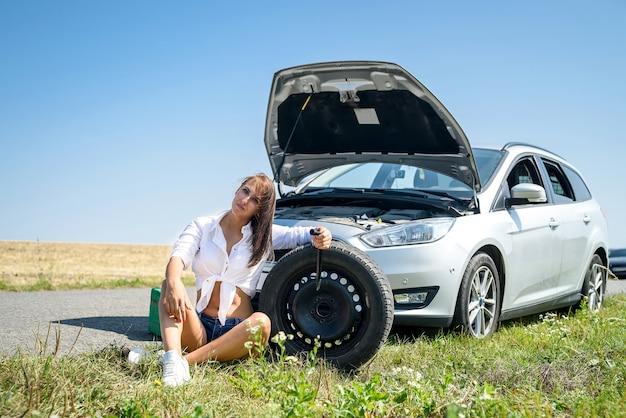 섹시 한 아름 다운 여자와 도로에 깨진 된 자동차. 도로 여행 문제 프리미엄 사진
